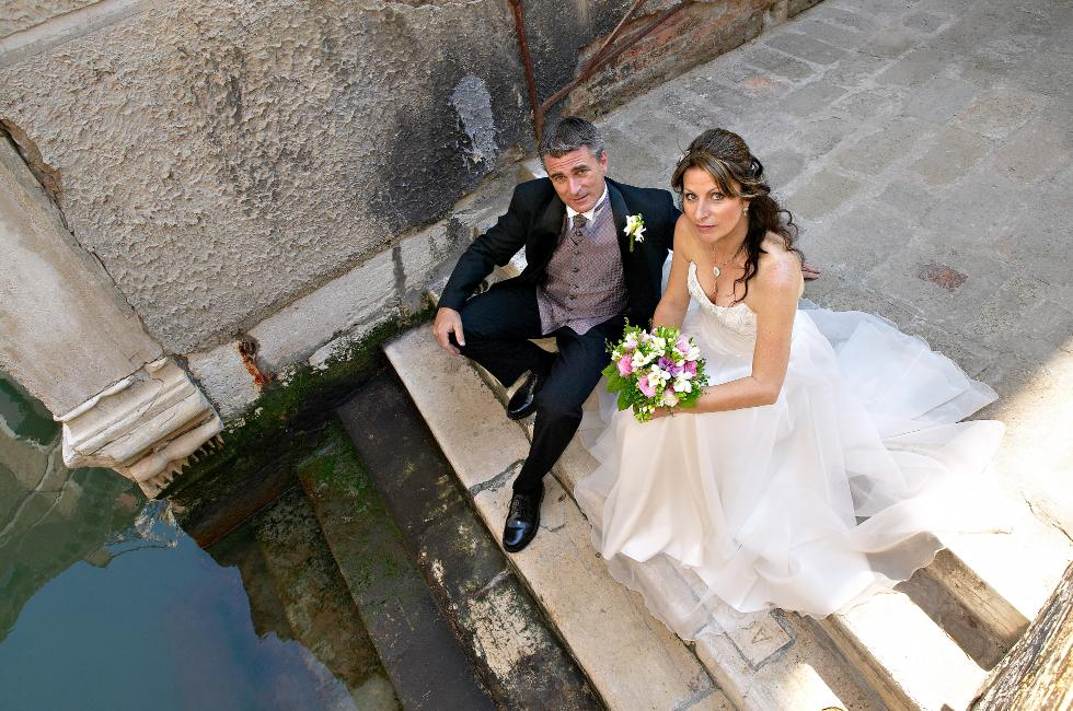bride and groom sitting near a Venetian canal